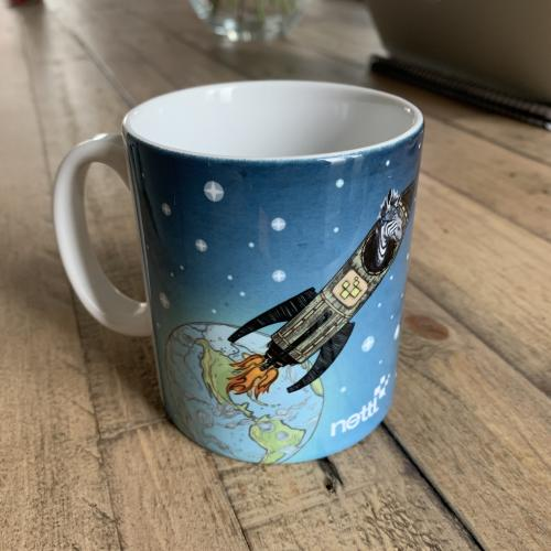Blue mug on wooden table with rocket ship